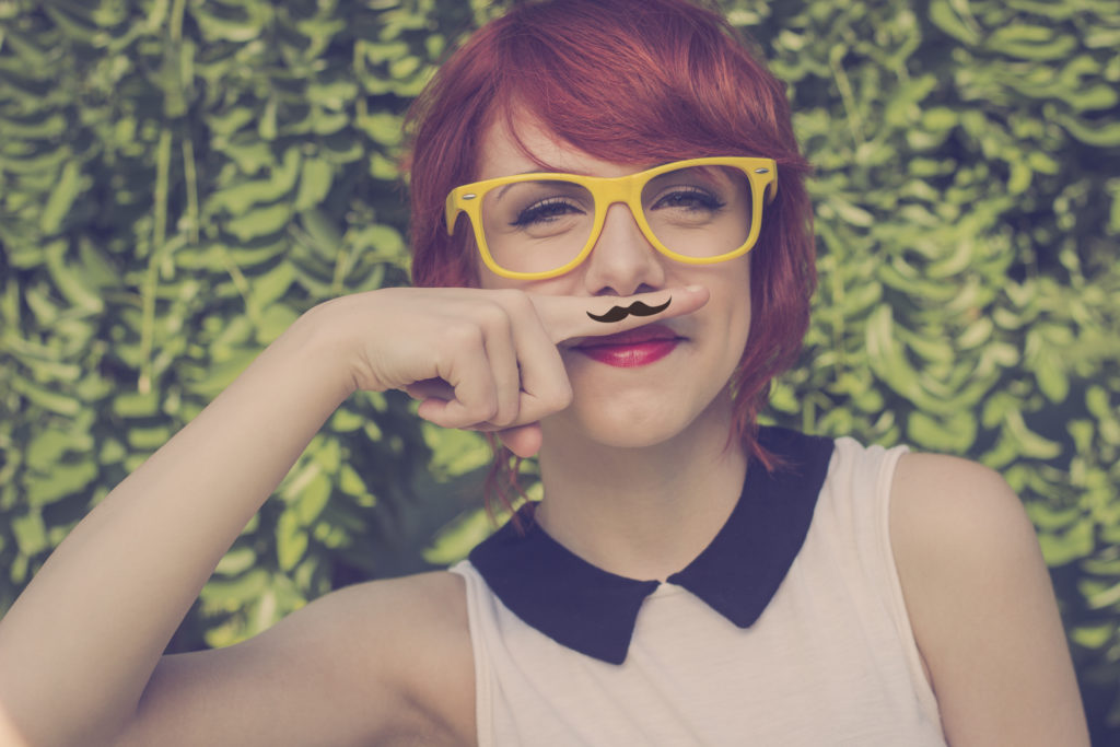 Cute hipster teenage girl with mustache hand drawn on a finger she placed over her lips cute and funny. Retro colors